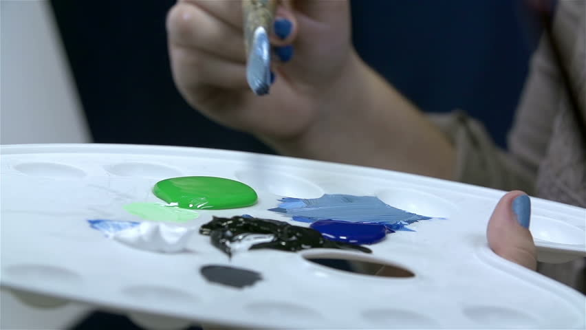 Woman hand picking color from palette and coloring canvas - HD stock video clip