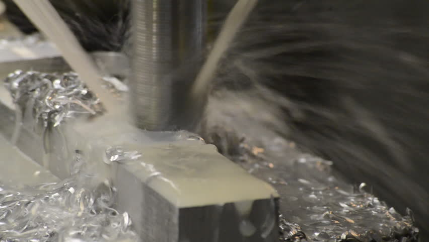 Large drill milling shapes out of a metal piece on a CNC machine