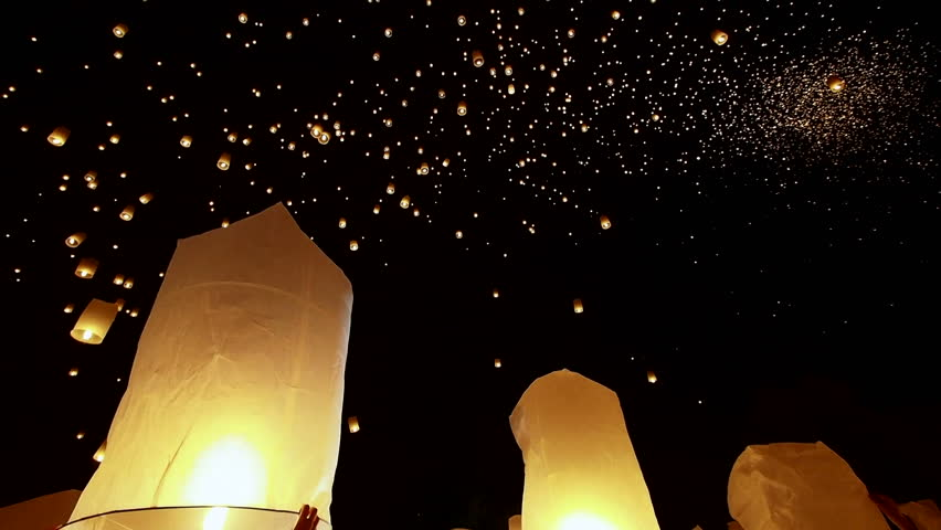 Hands releasing hot air balloons during the Loy Krathong / Yee Peng festival in Chiang Mai, Thailand.