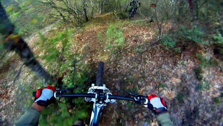 Extreme Mountain Bike race. View from handlebars of man on bike on dirt track