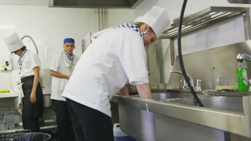 Team of chefs in a professional kitchen doing dishes and cleaning the kitchen equipment. In slow motion. - HD stock video clip