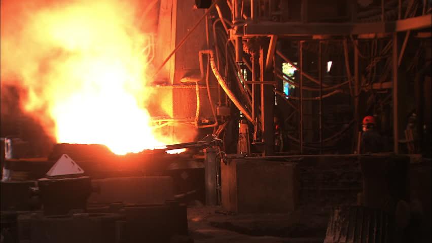 Steel workers are silhouetted in front of glowing red molten metal while working in the mill - HD stock footage clip