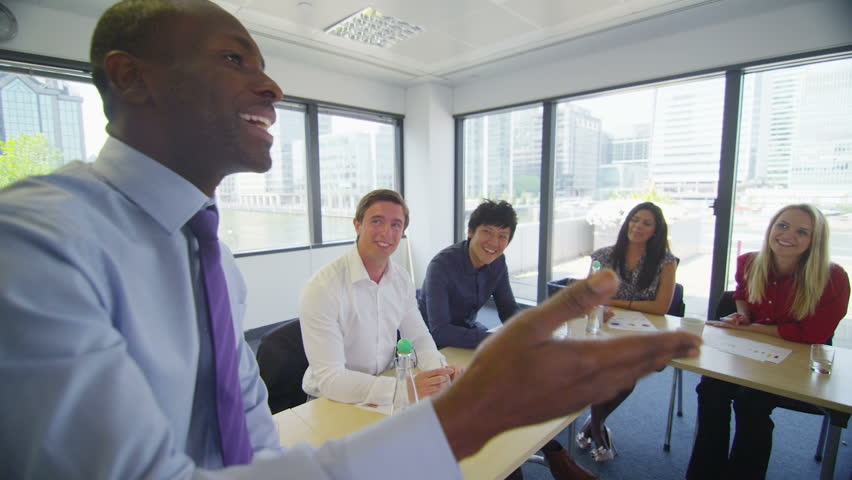 Attractive mixed ethnicity business team in boardroom meeting or training seminar.