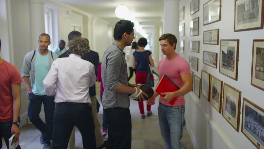 Two young male students greet each other as they meet up in the busy hallway of their college or university. In slow motion. | Shutterstock HD Video #5111837