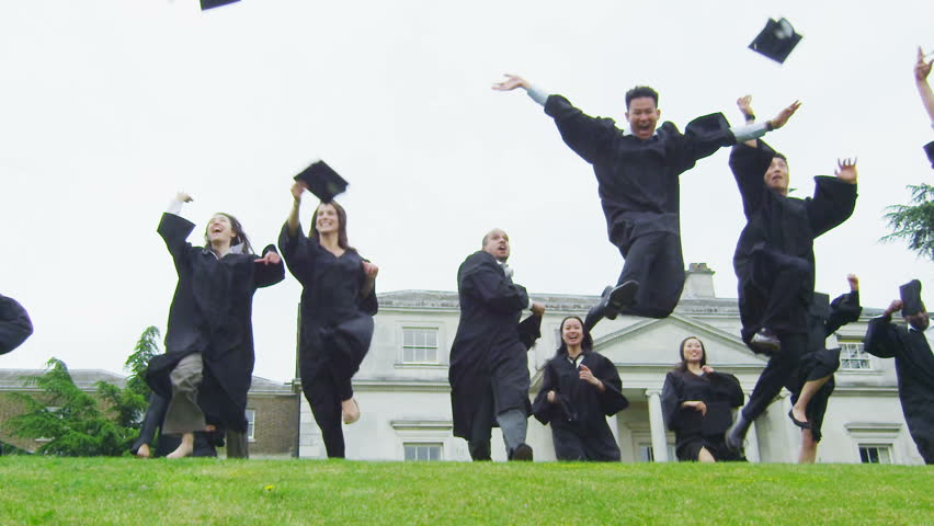 Happy and excited mixed ethnicity group of student friends on graduation day run through the natural green landscape of their college campus and throw their caps into the air. In slow motion.
