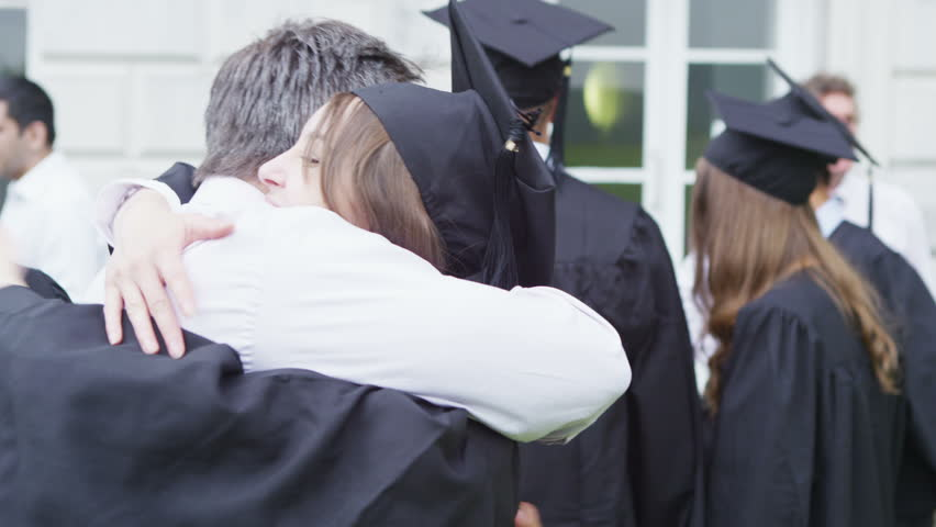 Happy students on graduation day are hugged and congratulated by proud parents