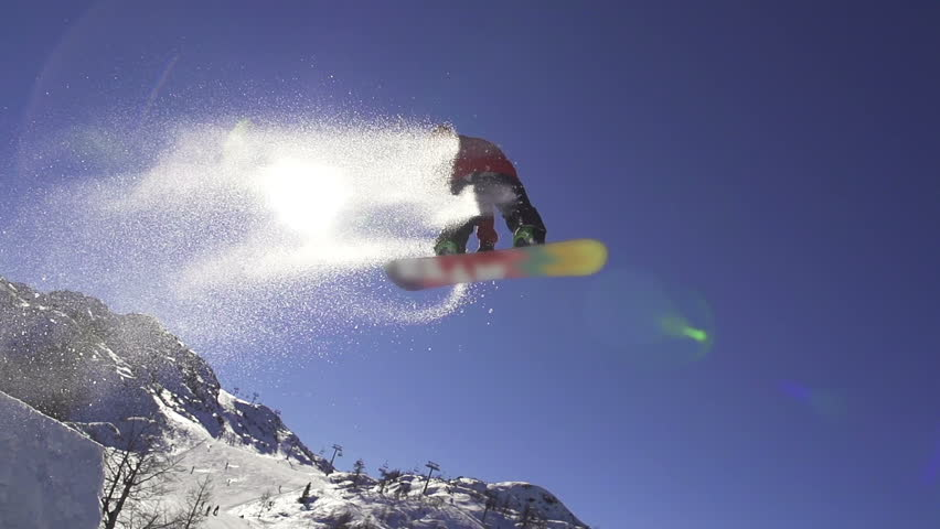 SLOW MOTION: Snowboarder jumping over the sun