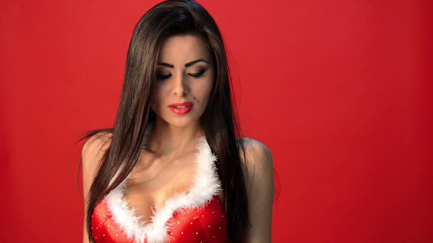 Sexy Brunette Woman in Red Christmas Outfit Posing Isolated and Sending Kisses
