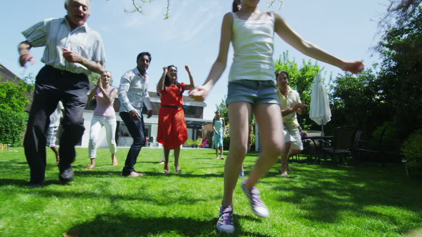 Happy mixed ethnicity group of friends and family with many generations, playing sports and having fun in the garden on a summer day. In slow motion.