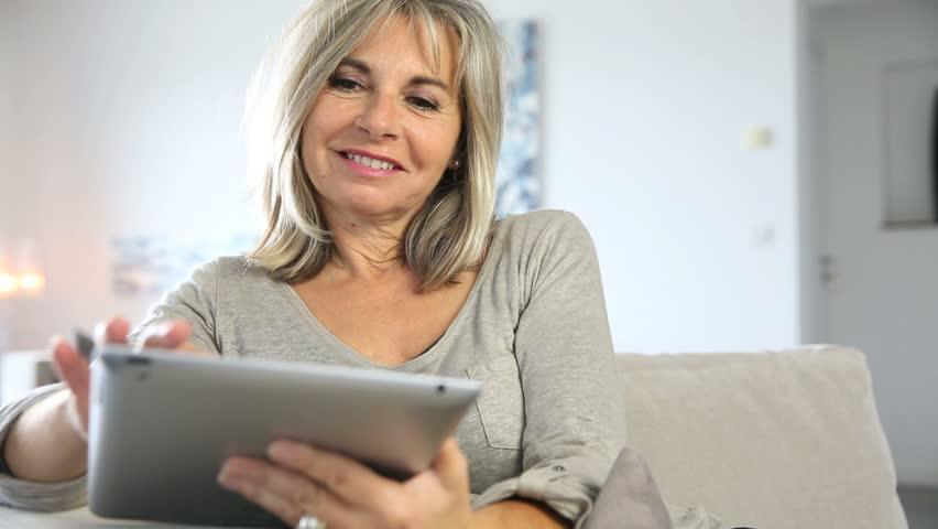 Senior woman in sofa websurfing on internet