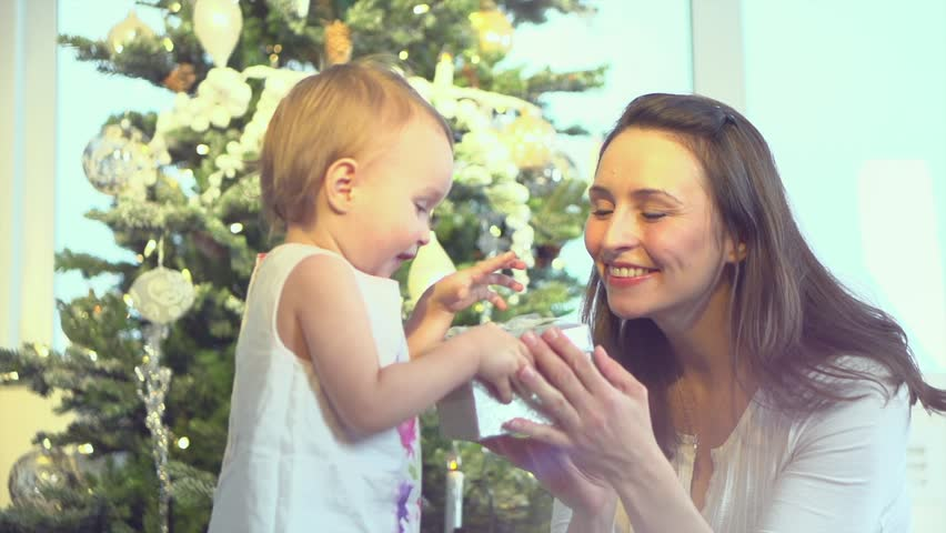 Happy Mother and Baby with Christmas Gift near the Christmas Tree at home. Child opening a Gift Box