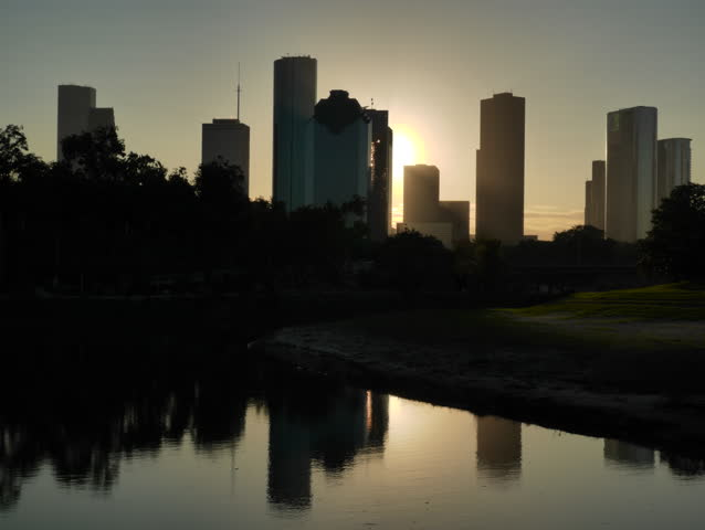 Houston, Texas - November 20, 2013 - Dawn timelapse of the Houston skyline silhouetted against the rising sun and reflected on the Buffalo Bayou. The sun is later clipped by dark rolling rain clouds.