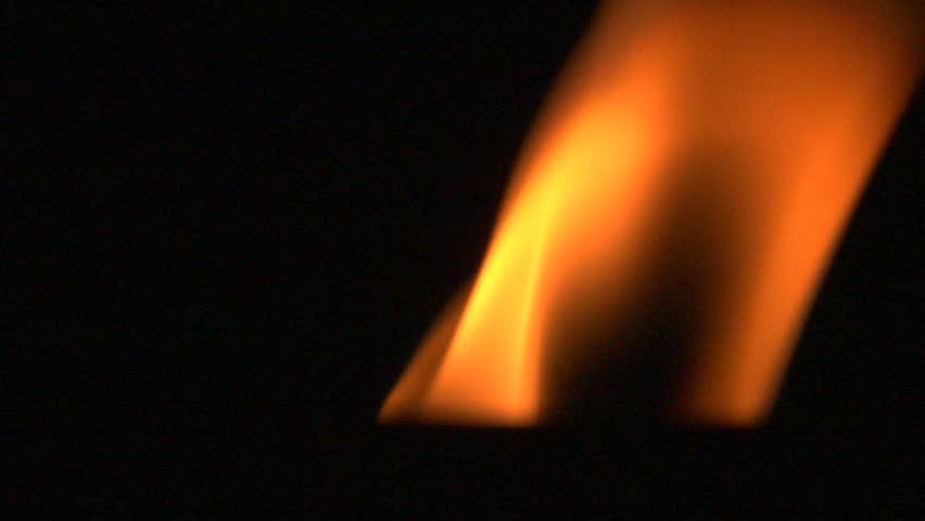 Close-up of burning candle isolated on black background