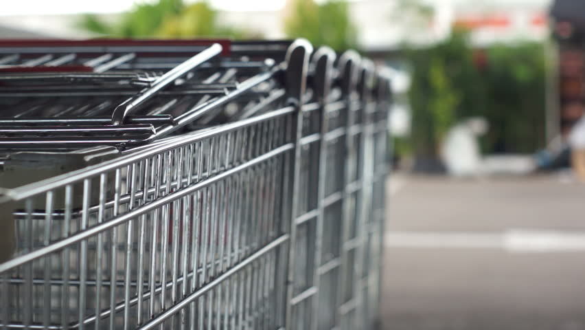 Short depth of field shot of a guy walking up to a row of shopping carts and pulling one out to go do some shopping in the supermarket. - HD stock footage clip