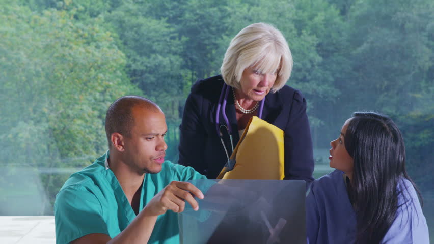 Medical team in modern glass building discussing the x ray of a patient - HD stock footage clip