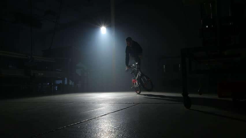 BMX rider doing tricks in dark warehouse - HD stock video clip