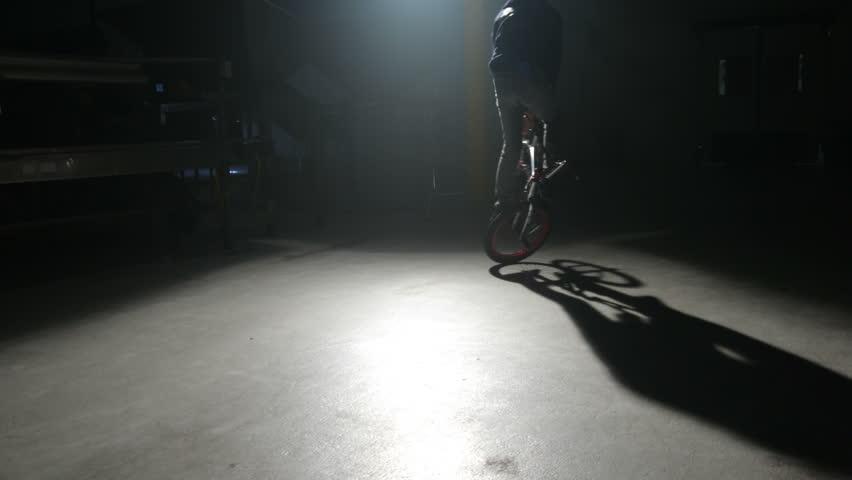 BMX rider doing tricks in dark warehouse - HD stock footage clip