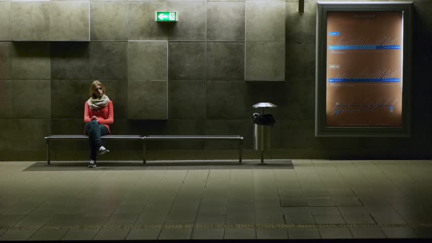 blonde sitting on a bench tube subway underground station carts passing by in the foreground