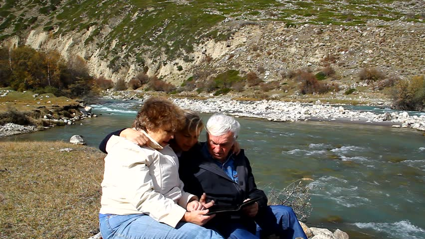 Happy elderly couple sitting on the bank of the river and look at the photo album   Shutterstock HD Video #5178338