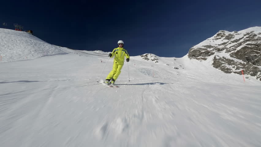 alpine skier skiing on slope in Austrian mountains on sunshiny day behind camera