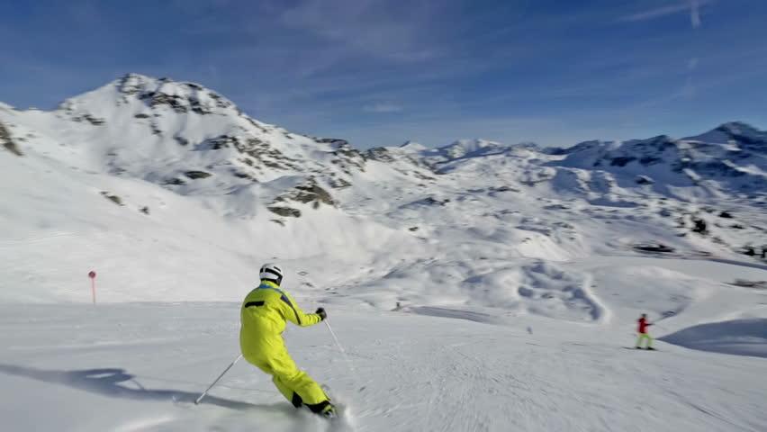 skier splashing snow on camera while skiing down ski slope