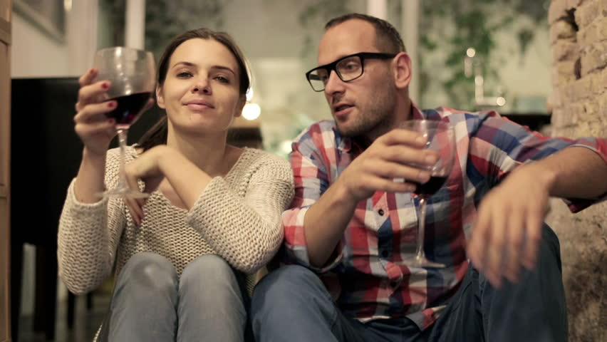 Happy attractive couple sitting on the floor and drinking red wine