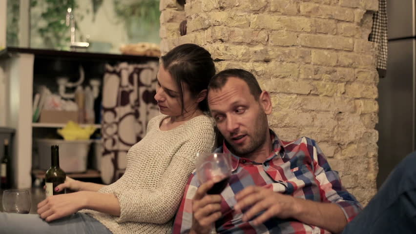 Drunk couple drinking wine and talking on the kitchen floor  - HD stock video clip