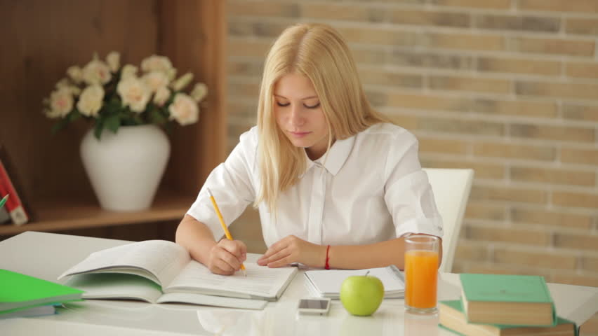 Charming blonde girl sitting at desk writing in notebook looking at camera and smiling stock - Desk girl image in ...