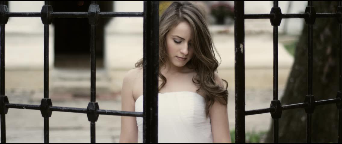 Beautiful bride in her wedding dress next to an iron gate
