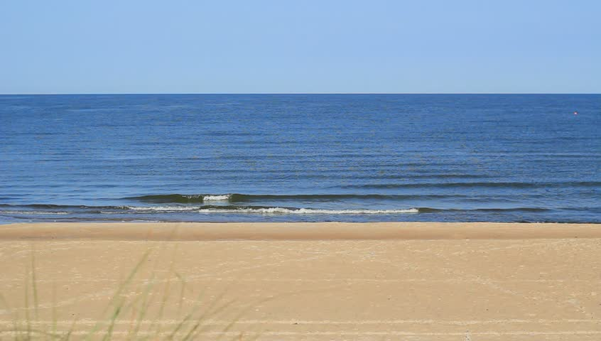 Wide, static beach scene with blue sky, sand, sea water, waves. Perfect scene for background use. - HD stock video clip