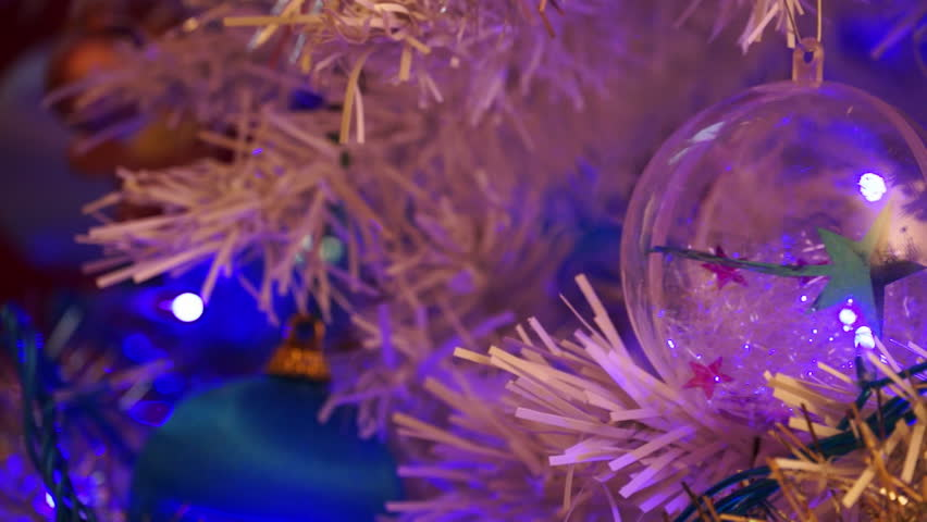 Christmas tree. Close-up on transparent ball. Blinking tinsel. - HD stock video clip
