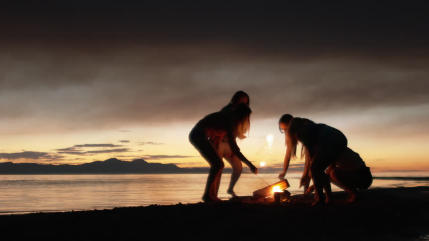 Group of Five Teenage Girls Lighting Sparklers At A Campfire On The Beach At Dusk - HD stock video clip