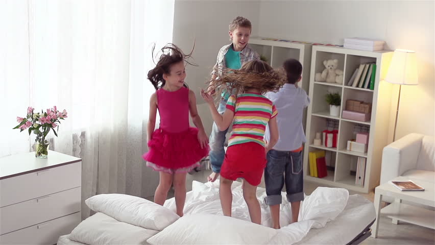 Four energetic friends spending their weekend together jumping on the bed