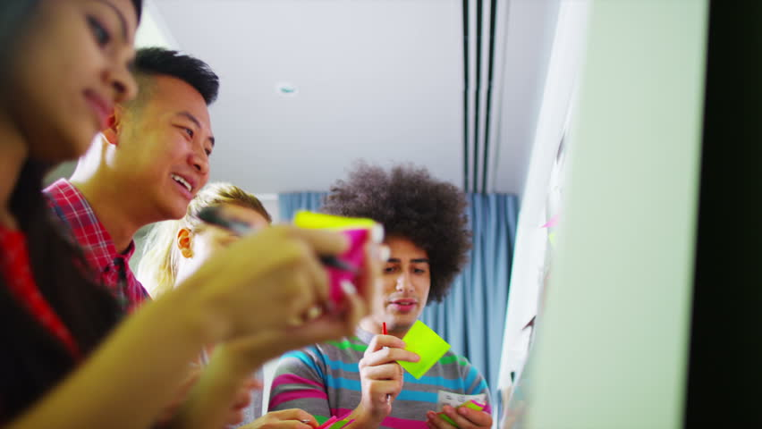 Young creative business team brainstorming with the use of post-it notes - HD stock footage clip
