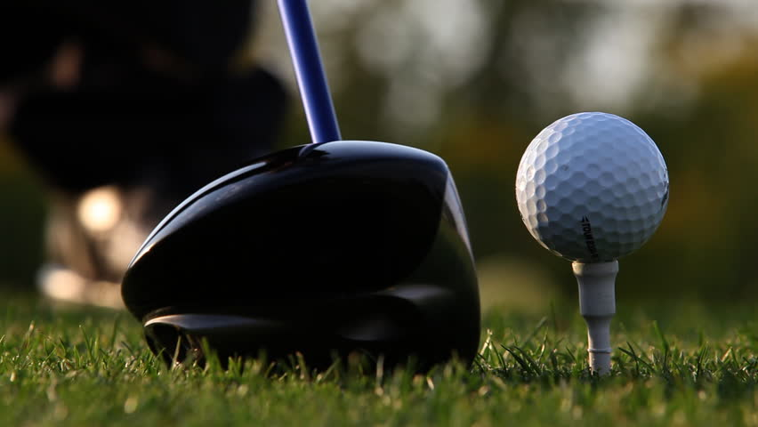 Close up of golf ball sitting on tee with driver swings and hits the ball - HD stock footage clip