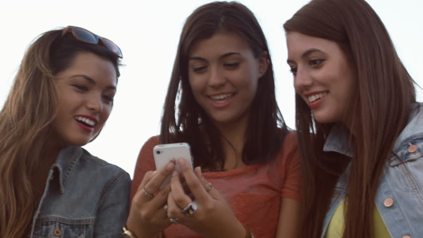 Teen Girls Amused By Something They See On A Cell Phone