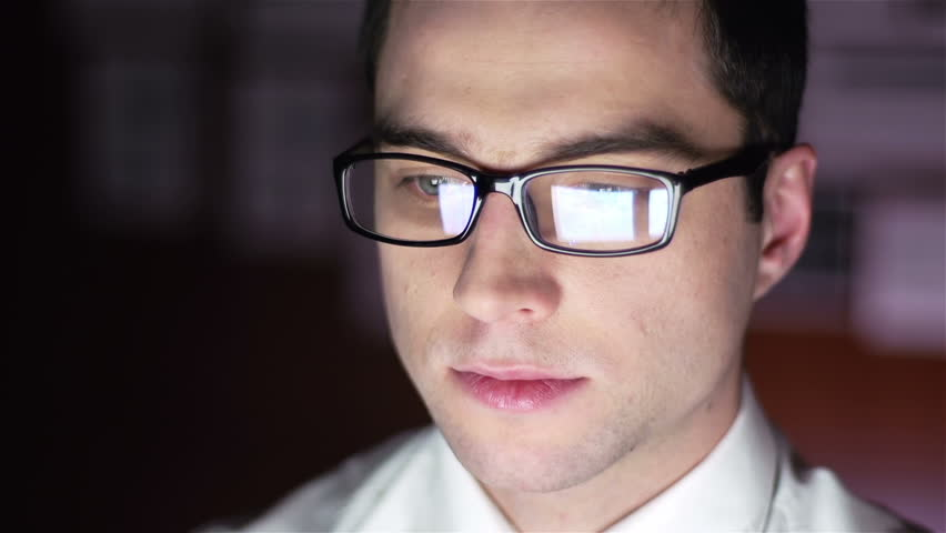 Close-up of a financial broker with stock exchange data reflecting in his glass lenses