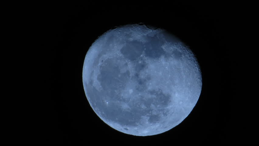 TIME LAPSE of a very large blue moon as it travels across the night sky shot with a 1200mm telephoto lens - HD stock video clip
