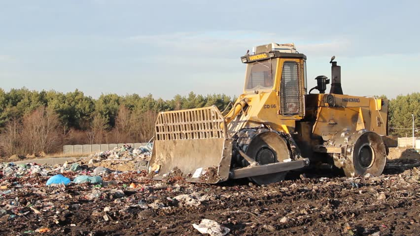 Landfills With Tractors : Bulldozer tractor moves non biodegradable garbage at