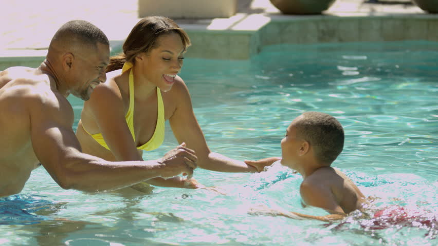 Young African American family spending time together outdoors home swimming pool shot on RED EPIC, 4K, UHD, Ultra HD resolution - 4K stock video clip