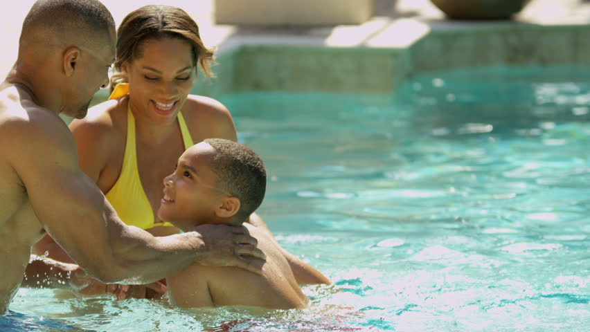 Happy young African American family enjoying healthy swimming lifestyle outdoor pool luxury vacation accommodation shot on RED EPIC, 4K, UHD, Ultra HD resolution - 4K stock footage clip