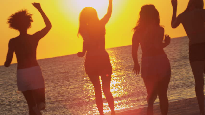 Young people in silhouette enjoying time together having fun beach break at sunset running to ocean shot on RED EPIC, 4K, UHD, Ultra HD resolution