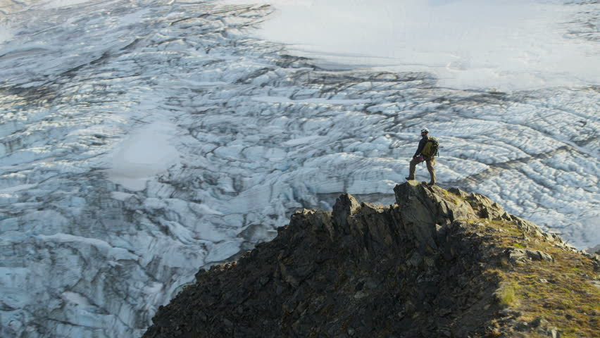 Aerial view of male mountain climber in summer enjoying success high Peaks Troublesome Glacier Chugach Mountains South Central Alaska, USA shot on RED EPIC, 4K, UHD, Ultra HD resolution