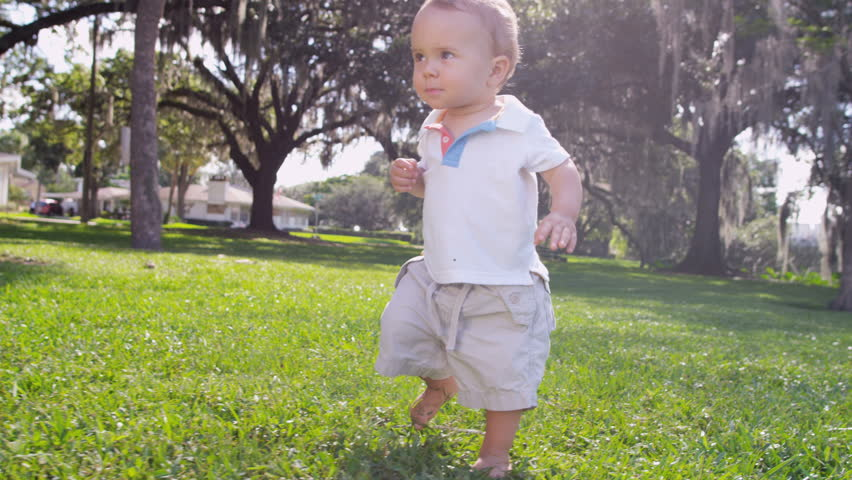 Smiling male Caucasian toddler child slowly walking barefoot by himself on grass outside park slow motion shot on RED EPIC, 4K, UHD, Ultra HD resolution