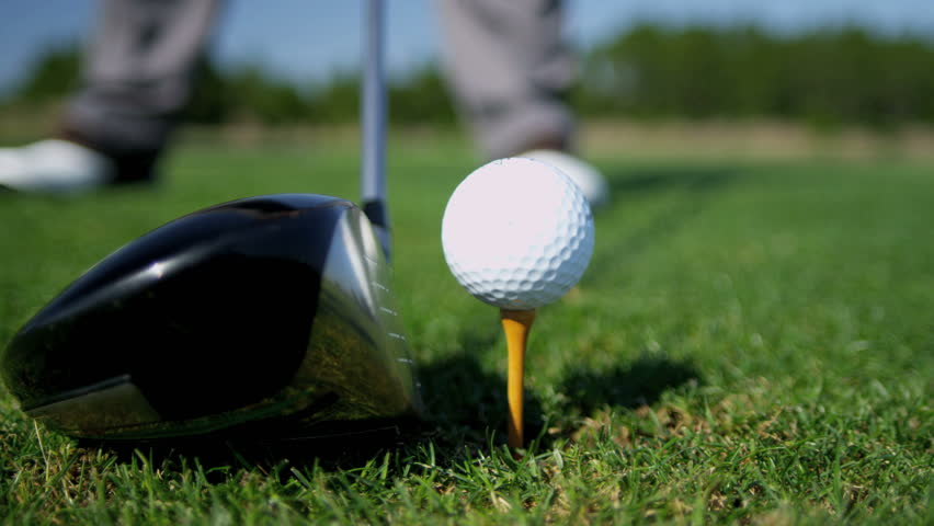 Close up ball on tee retired golfer taking swing hitting golf ball off tee on golf course feet only shot on RED EPIC, 4K, UHD, Ultra HD resolution