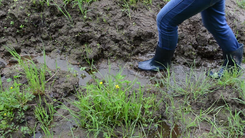 Woman legs with gumboots rubber boots walk on wet dirt soil mud swamp marsh and leaves foot prints marks. - HD stock footage clip