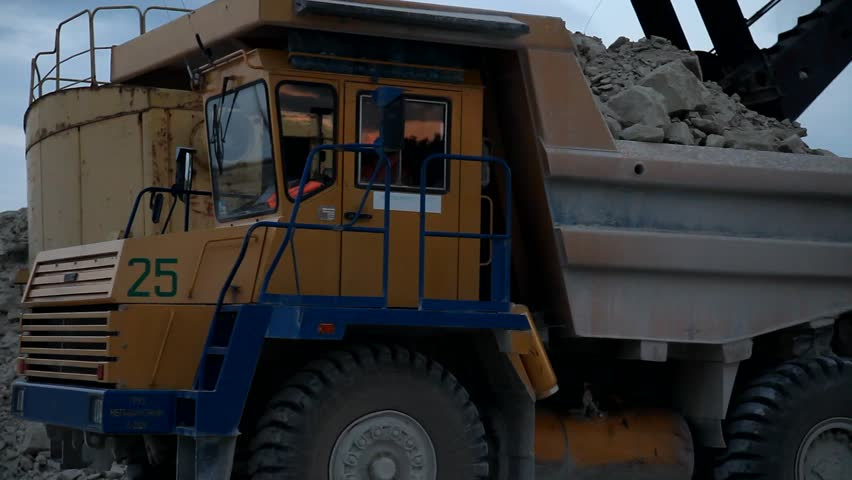 Heavy mining dump truck being loaded with iron ore - HD stock video clip