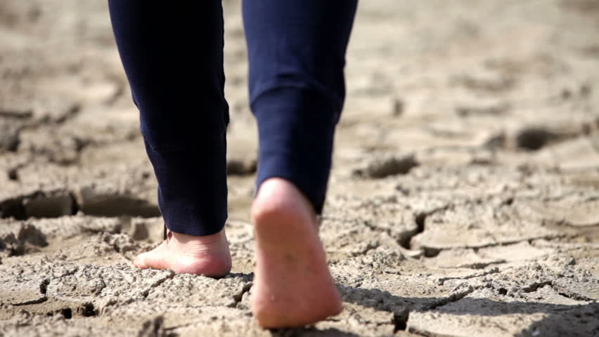 Female barefooted person walking across dry and cracked soil