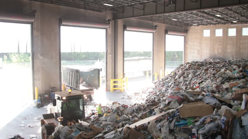 A large tractor pushes trash into the recycling building. - HD stock video clip