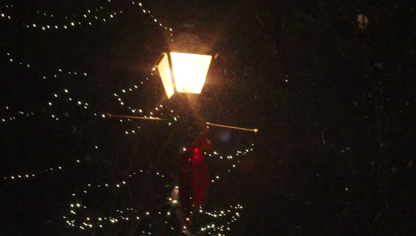 Snow falling by lighted post lantern with christmas lights - HD stock video clip